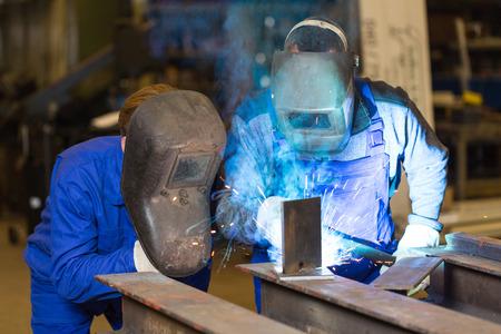 soldadura: Dos trabajadores de la construcci�n de acero de soldadura de piezas met�licas
