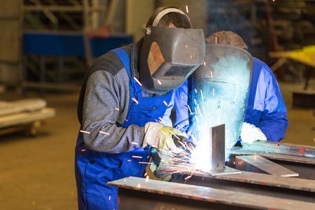 metal worker: Two steel construction workers welding metal pieces Stock Photo