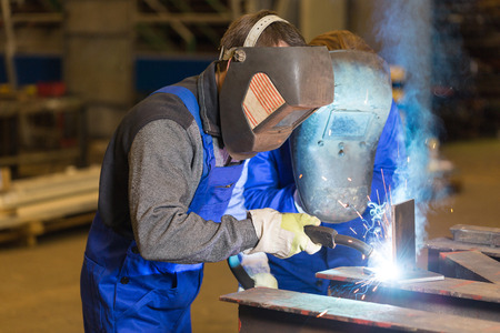 welding mask: Two steel construction workers welding metal pieces Stock Photo