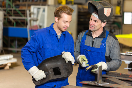 welding mask: Instructor teaching trainee or worker how to weld metal