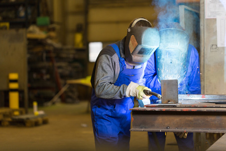 Two steel construction workers welding metal in workshop