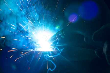 Closeup of welding metal with arc, sparks and torch Stock Photo