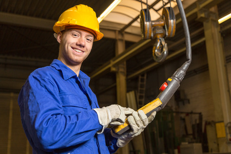 assembly hall: Construction worker operating a crane in assembly hall Stock Photo