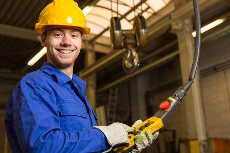obrero: Trabajador de la construcci�n que opera una gr�a en sala de actos Foto de archivo