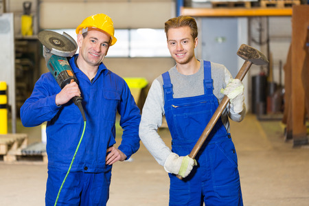 sledge hammer: Two steel construction workers posing with angle grinder and sledge hammer Stock Photo