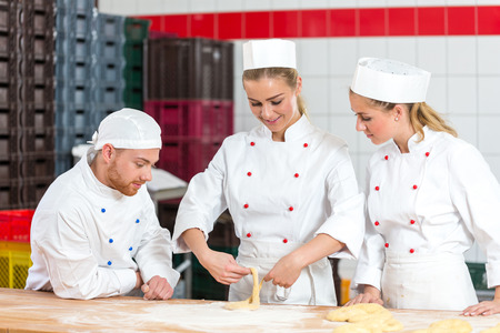 sceptical: apprentice in bakery trying to make pretzels and sceptical bakers are watching