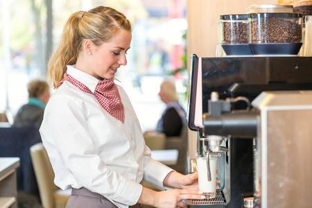woman shop: Waitress working at coffee machine in bakery, bistro or cafe Stock Photo
