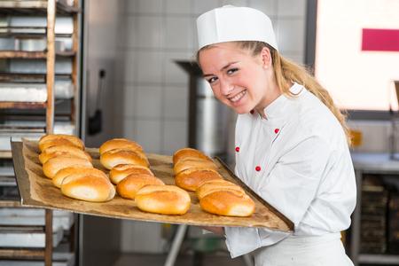 パン屋やベーカリーの焼きたてのパン、パン、パンの臭いがする見習い 写真素材