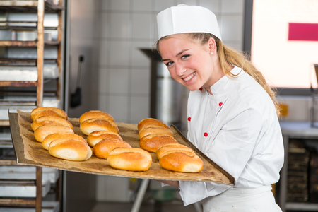 Baker or apprentice in bakery smelling fresh pastry, bread and buns
