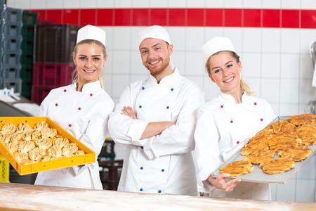 baking tray: Bakers in a bakery posing with baking tray Stock Photo