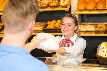 paper bag: Shopkeeper or saleswoman in bakery hand bag of bread to customer