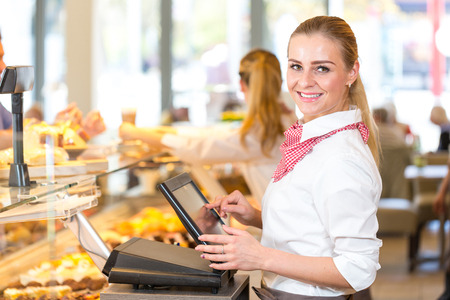 금전 등록기에서 일하는 빵집에서 장사꾼 또는 판매원