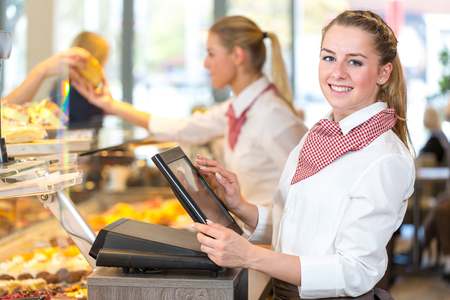 Shopkeeper or saleswoman at bakery working at cash register 스톡 콘텐츠
