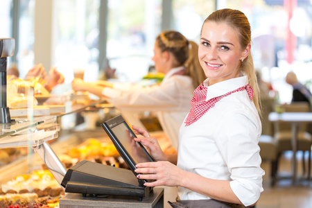 Shopkeeper or saleswoman at bakery working at cash register Stock Photo