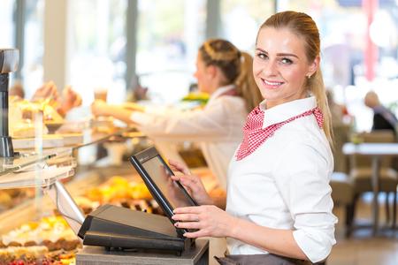 caja registradora: Tendero o dependienta en la panadería que trabaja en la caja registradora