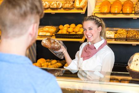 tranches de pain: Commer�ant en boulangerie pr�sentant miche de pain � la client�le