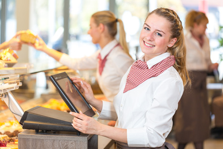 Shopkeeper or saleswoman at bakery working at cash register Stockfoto