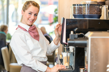 bistro: Waitress working at coffee machine in bakery, bistro or cafe Stock Photo