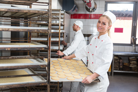 fresh bakery: Baker presenting tray with pastry or dough in bakery