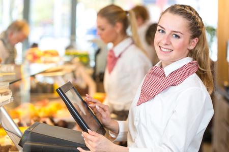 Commerçant ou vendeuse au boulangerie travailler à la caisse