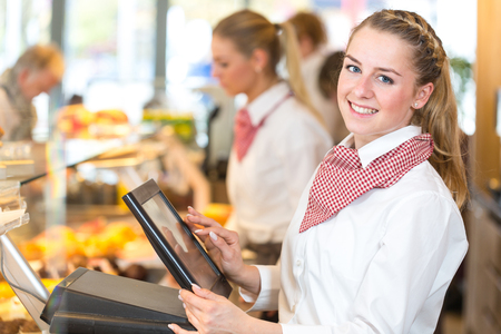 Shopkeeper or saleswoman at bakery working at cash register Standard-Bild