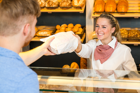 saleswoman: Shopkeeper or saleswoman in bakery hand bag of bread to customer