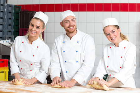 kneading: Three bakers in bakery kneading fresh dough Stock Photo