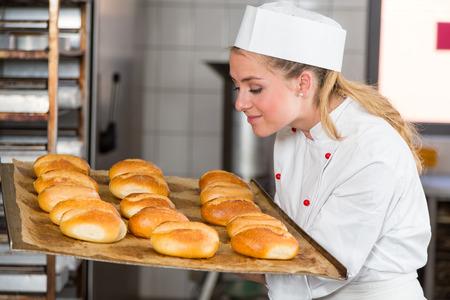 panadero: Panadero o aprendiz de panadería oliendo pastelería fresca, pan y bollos