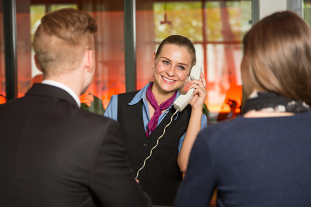 telephone: Receptionist with telephone assisting guests in a hotel