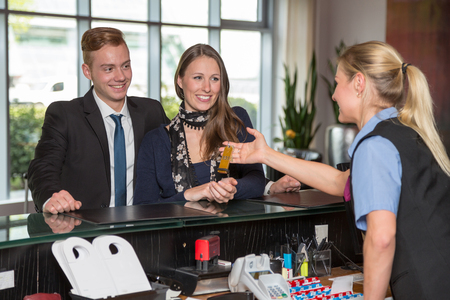 hotel receptionist: Hotel receptionist handing over key to two customers Stock Photo