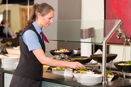 salad buffet: Waitress or catering professional putting food into a buffet Stock Photo