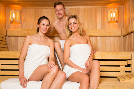 Two women and one man posing in wellness sauna Фото со стока