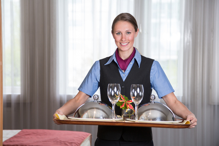 hotel room: Maid in a hotel posing with tray in bedroom