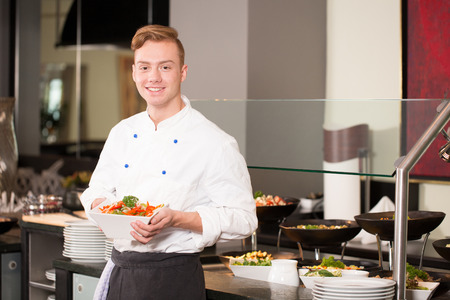 cook: cook or chef from catering service posing with food in front of buffet