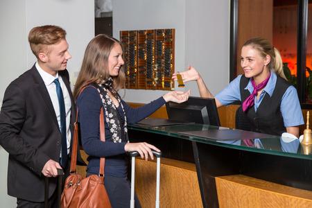 recepcion: recepcionista en la recepción del hotel entrega una clave para invitados o clientes