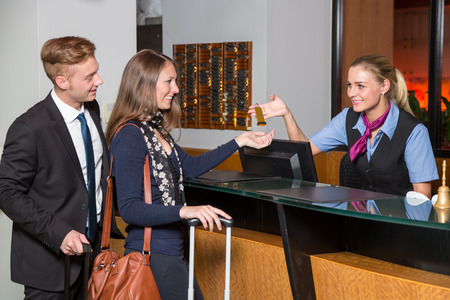 receptionist at hotel reception handing over a key to guest or customer Imagens - 47489039