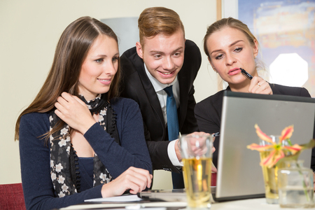 presenting: Team discussing and brainstorming together at a computer Stock Photo