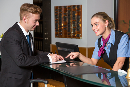 arrival: Guest or customer at hotel signs check-in form and receptionist is assisting him