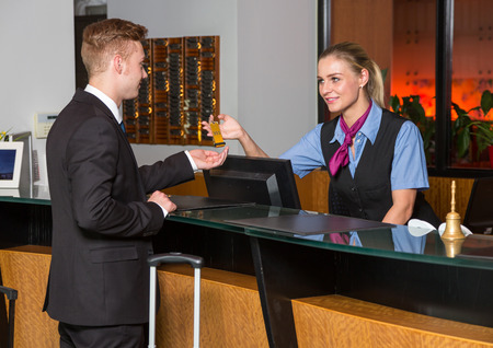 hotel receptionist: receptionist at hotel reception handing over a key to guest or customer