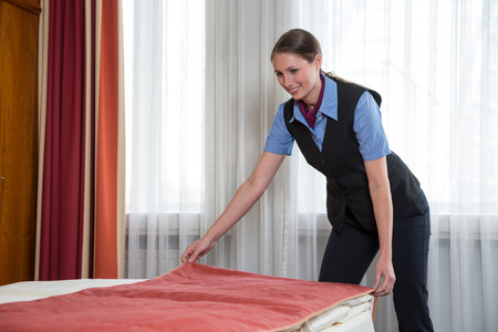 room service: Maid or room service making the bed in a hotel room Stock Photo