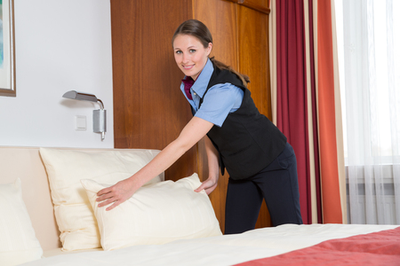 accomodation: Maid or room service making the bed in a hotel room Stock Photo