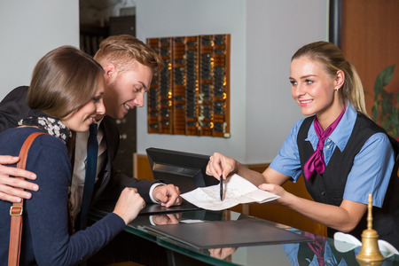 hotel receptionist: receptionist at hotel showing guest something on a map Stock Photo