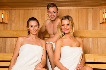 hot guy: Two women and one man posing in wellness sauna Stock Photo