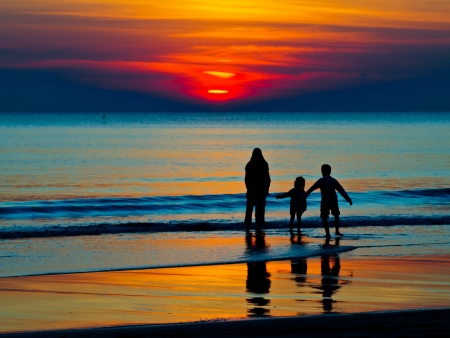 silhouette of a family in the sea Stock Photo