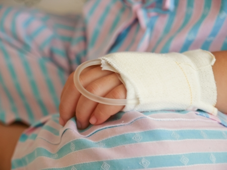hand of sick Little girl in hospital bed Stock Photo