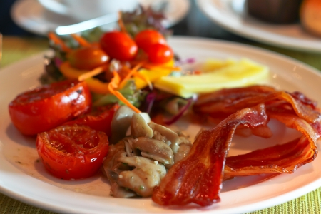 English Breakfast with grilled tomato , bacon ,mushrooms,chese and salad on Table photo