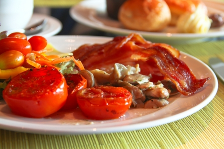 English Breakfast with grilled tomato , bacon ,mushrooms,chees and salad on Table