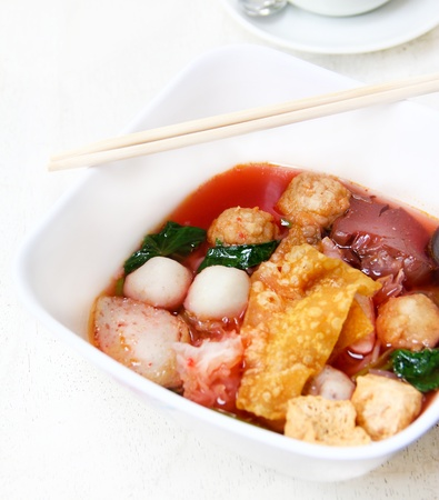 Popular thai fusion food, yen ta four  is Chinese-style rice noodles in sour spicy soup with red sauce and topped with seafood and vegetables