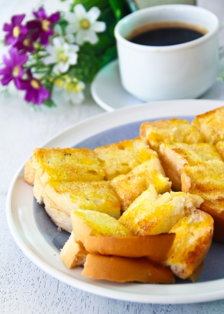 White bread toast with sugar and cup of coffee on table
