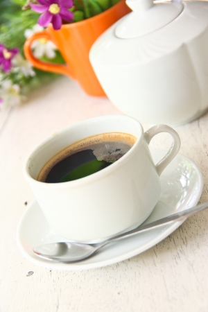 A CUP OF COFFEE ON WHITE TABLE